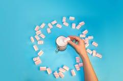 圣诞节热的饮料可可粉咖啡或巧克力与牛奶奶油和蛋白软糖在一小透明杯在蓝色背景 免版税库存照片