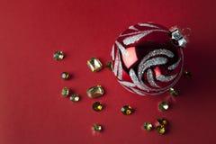圣诞节玩具和金刚石在红色背景 免版税库存照片