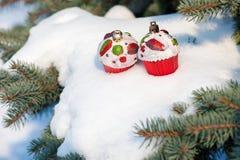 圣诞节玩具在与雪的冬天树结块 免版税图库摄影