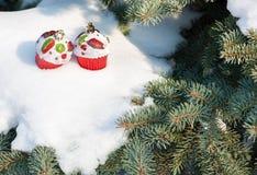 圣诞节玩具在与雪的冬天树结块 免版税库存照片