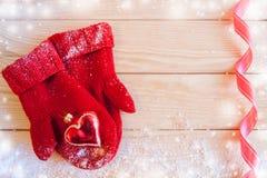 圣诞节玩具心脏在红色在木桌上的被编织的手套放置与雪、拷贝空间和红色波浪丝带 库存照片