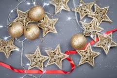 圣诞节玩具金黄星和球在灰色背景 免版税图库摄影
