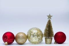 圣诞节玩具,连续站立金黄,红色,银色颜色和金黄的树许多闪光球  新年度 在一个灰色背景 免版税库存图片