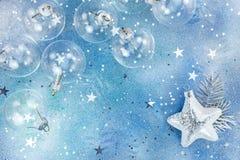 圣诞节玻璃球和发光的银色星在蓝色背景w 免版税图库摄影