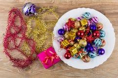 圣诞节球、纸板箱和响铃在白色盘,闪亮金属片 图库摄影
