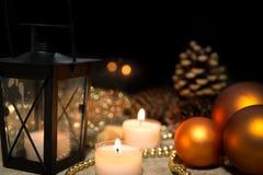 圣诞节球、蜡烛、一个灯笼和珍珠在木桌上 库存图片