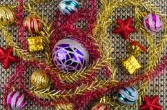圣诞节球、goldish箱子、红色星和闪亮金属片在席子 库存照片