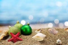 圣诞节球和壳在海滩 免版税库存图片