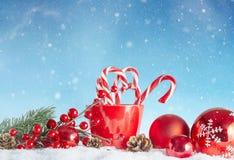 圣诞节球和棒棒糖在多雪的冬天设置 库存图片