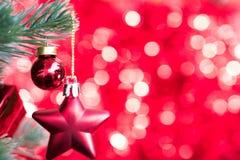 圣诞节球装饰品在与红色bokeh后面的杉树装饰 库存图片