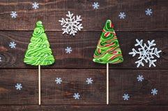 圣诞节甜点:以杉树的形式明亮的色的在黑暗的木背景的糖果和雪花 庆祝的backgroun 免版税库存图片