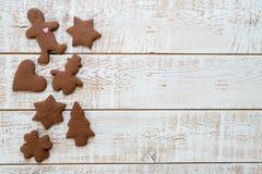 圣诞节用不同的形状的姜饼曲奇饼在一张白色葡萄酒木桌 库存照片