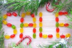 圣诞节由与多雪的杉树分支的焦糖糖果做的标志销售在木背景 免版税库存照片