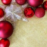 圣诞节电灯泡和星装饰品框架在金子闪烁Backgrou 免版税库存照片
