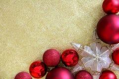圣诞节电灯泡和星装饰品框架在金子闪烁Backgrou 免版税库存图片