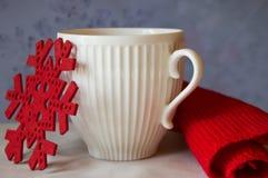 圣诞节白色杯子红色雪花和编织围巾的概念 免版税库存照片