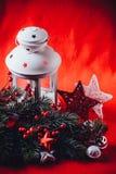 圣诞节白色灯笼站立与在它的一个灼烧的蜡烛与一个杉树分支和编织星在红色背景 免版税库存图片
