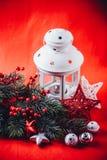 圣诞节白色灯笼站立与在它的一个灼烧的蜡烛与一个杉树分支和编织星在红色背景 库存照片
