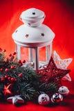 圣诞节白色灯笼站立与在它的一个灼烧的蜡烛与一个杉树分支和编织星在红色背景 免版税库存照片
