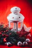 圣诞节白色灯笼站立与在它的一个灼烧的蜡烛与一个杉树分支和编织星在红色背景 图库摄影