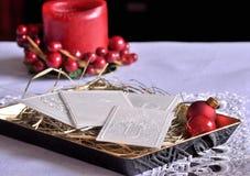 圣诞节白色薄酥饼和蜡烛在桌上 Oplatek 库存图片