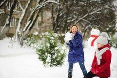 圣诞节白色 女孩使用与雪球的母亲在冬天公园 库存照片