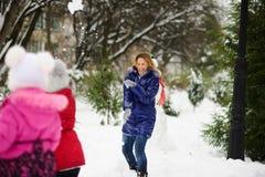 圣诞节白色 女孩使用与雪球的母亲在冬天公园 库存图片