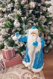 圣诞节的一个圣诞老人玩偶在一个绿色圣诞树和被包装的圣诞节礼物旁边 愉快的时间一起  免版税库存照片