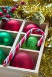 圣诞节的准备:欢乐球和棒棒糖在木箱在白色木桌上 库存图片