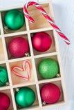 圣诞节的准备:欢乐球和棒棒糖在木箱在白色木桌上 免版税库存图片