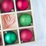 圣诞节的准备:欢乐球和棒棒糖在木箱在白色桌,正方形上 免版税图库摄影