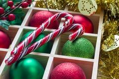 圣诞节的准备:欢乐球和棒棒糖在木箱 库存图片