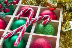 圣诞节的准备:欢乐球和棒棒糖在木箱 免版税图库摄影