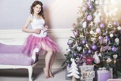 圣诞节的年轻美丽的孕妇与一美好的tre 免版税图库摄影