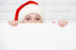 圣诞节的愉快的妇女与空白的空的白色海报 免版税库存照片