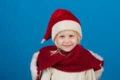 圣诞节的愉快的矮小的微笑的女孩在圣诞老人帽子 免版税库存照片