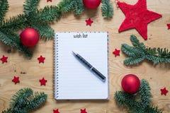 圣诞节的愿望在与圣诞节装饰的一个笔记薄 库存照片