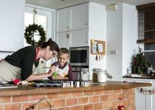 圣诞节的母亲和儿子烘烤在厨房里 免版税库存图片