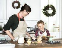 圣诞节的母亲和儿子烘烤在厨房里 库存照片