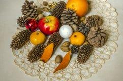 圣诞节的礼物在从苹果的餐巾,蜜桔,坚果,杏仁,用不同的具球果锥体的圣诞节玩具在胶合板 库存照片