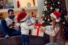 圣诞节的礼物-享用在圣诞节礼物的家庭 免版税图库摄影
