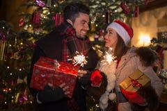 圣诞节的美丽的夫妇照明设备闪烁发光物在a前面 免版税库存图片
