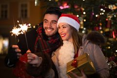 圣诞节的美丽的夫妇照明设备闪烁发光物在a前面 库存图片