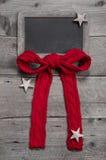 圣诞节的菜单板与红色丝带和星在灰色woode 免版税库存照片