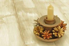 圣诞节的装饰元素 手工制造黏土烛台、蜡蜡烛和冷杉球果在轻的木背景 库存照片