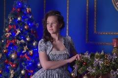 圣诞节的青少年的女孩在美丽的圣诞树g 免版税库存照片