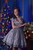 圣诞节的青少年的女孩在美丽的圣诞树g 免版税图库摄影
