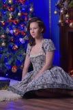 圣诞节的青少年的女孩在美丽的圣诞树g 图库摄影