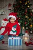 圣诞节的,打开的礼物小男孩 免版税图库摄影