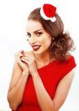 圣诞节的年轻人相当愉快的微笑的深色的妇女在圣诞老人 免版税图库摄影